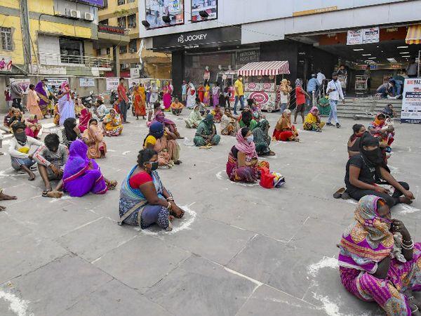 पटना में सोशल डिस्टेंसिंग का पालन कर रहे ये लोग सरकारी राशन लेने आए हैं। इंतजार लंबा करना पड़ा तो जमीन पर ही बैठ गए।