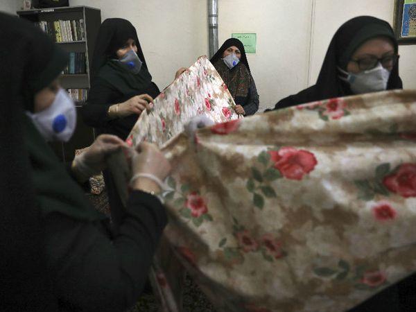 इरान की राजधानी तेहरान में मस्जिद में अस्पतालों के लिए चादरें तैयार करती हुईं स्वयंसेवी महिलाएं।