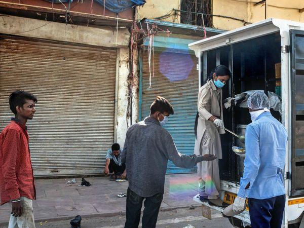 दिल्ली में जरूरतमंदों को खाना खिलाते लोग। दिल्ली सरकार रोज एक लाख से ज्यादा भूखे लोगों को खाना खिला रही है।