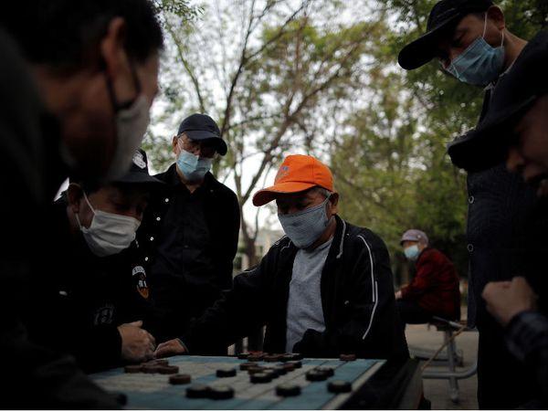 बीजिंग के एक पार्क में मास्क पहनकर कैरम खेलते कुछ लोग।
