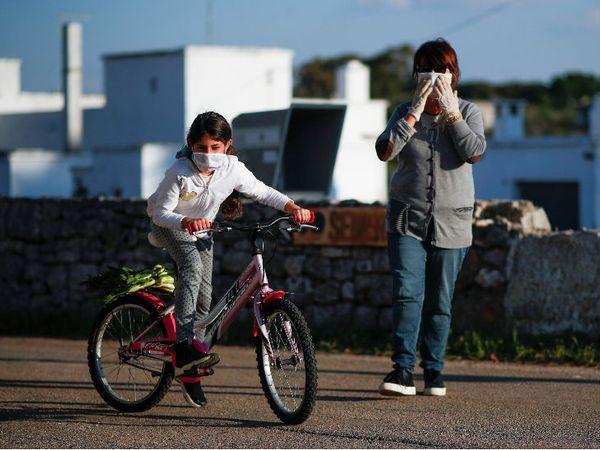 यह तस्वीर 24 अप्रैल की है। इटली के एक शहर में बच्ची और उसकी दादी मास्क पहनकर घूमने निकले हैं। सरकार यहां 4 मई से लॉकडाउन में ढील देने की योजना बना रही है।