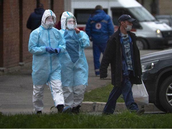 रूस के सेंटपिटसबर्ग में पोक्रोस्कोवा हॉस्पिटल के पास से प्रोटेक्टिव सूट पहनकर गुजरता स्वास्थ्यकर्मी।