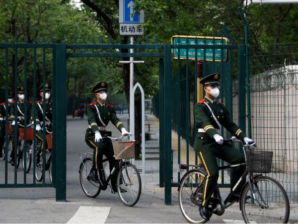 बीजिंग में मास्क पहने पैरामिलिट्री अफसर साइकिल से जाते हुए। देश में 77 हजार 610 मरीज ठीक हो चुके हैं।