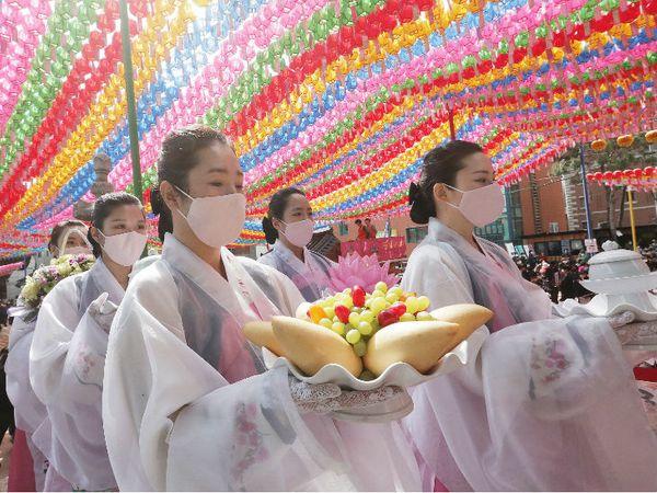 महामारी के बीच सियोल के चोगेस्सा मंदिर में बुद्ध जयंती मनाने के लिए जुटे लोग। देश में संक्रमण के मामले काफी कम हो गए हैं।