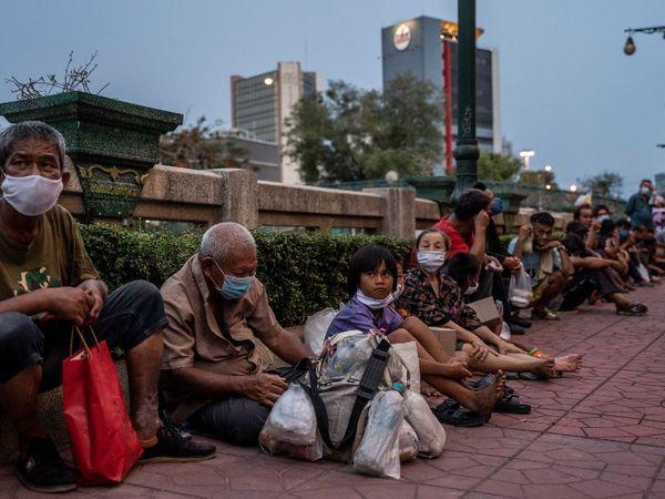 बैंकॉक में फूड डिस्ट्रीब्यूशन सेंटर पर खाने के लिए लाइन में लगे लोग।