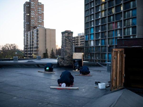 मिनीपोलिस में रमजान के पहले हफ्ते में दर अल-हिज्राह मस्जिद के सदस्य सूर्य अस्त होने के बाद छत पर नमाज पढ़ते हुए।