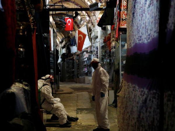 तुर्की के इस्तांबुल में ग्रांड बाजार को डिसइन्फेक्ट करते हुए जब मेडिकल वर्कर थक गए तो वह आराम करने लगे। बाजार को 1 जून से खोलने की तैयारी है।