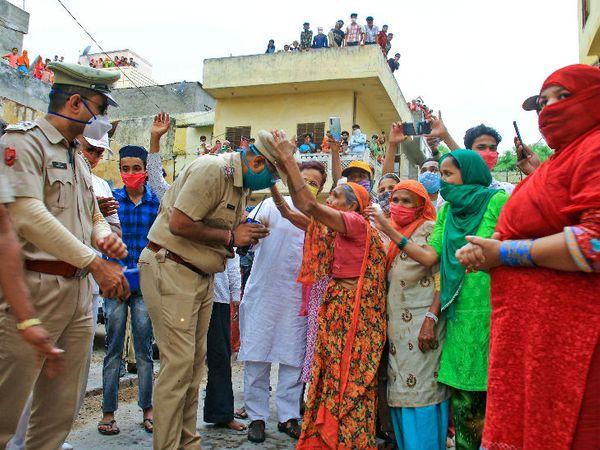 जयपुर में फ्लैग मार्च निकालते पुलिसवालों को आशीर्वाद देती महिलाएं। यहां कोरोना के 1200 से ज्यादा मरीज मिल चुके हैं। यह राजस्थान में संक्रमण से सबसे ज्यादा प्रभावित जिला है।