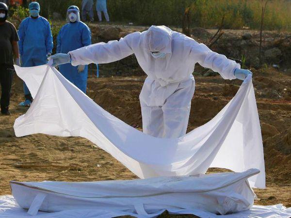 दिल्ली में सोमवार को एक संक्रमित मुस्लिम महिला की मौत हो गई। दफनाने से पहले शव पर चादर डालता हेल्थ वर्कर। - Dainik Bhaskar