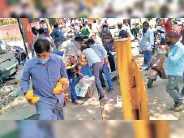 जगतपुरी क्षेत्र में रेहड़ी से आम लूटकर ले जाती लोगों की भीड़। - Dainik Bhaskar
