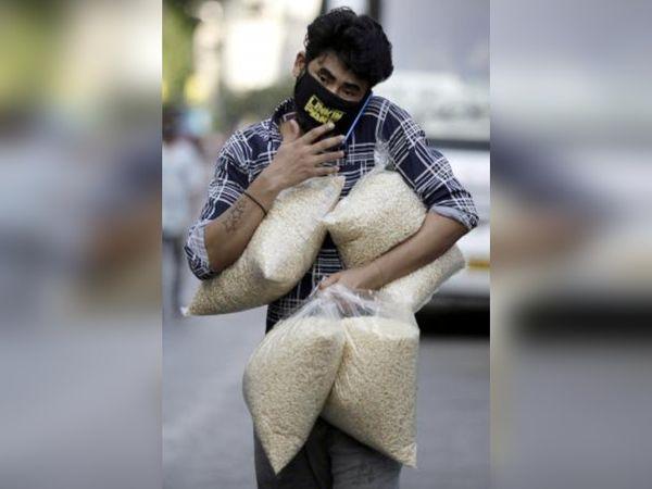 यह तस्वीर मुंबई की है। यहां पश्चिम बंगाल का एक प्रवासी मजदूर घर के लिए राशन ले जाता हुआ। - Dainik Bhaskar