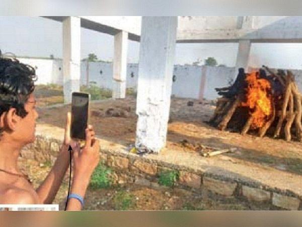 यह तस्वीर महासमुंद की है। ओडिशा के गंजाम निवासी प्रफुल स्वाईं सूरत की साड़ी मिल में काम करता था। 23 मई को वह बेटे के साथ ट्रेन से गांव आ रहा था, रास्ते में उसकी मौत हो गई थी। मंगलवार को उसका अंतिम संस्कार किया गया। पत्नी और परिजन ने वीडियो कॉल के जरिए अंतिम दर्शन किए। - Dainik Bhaskar