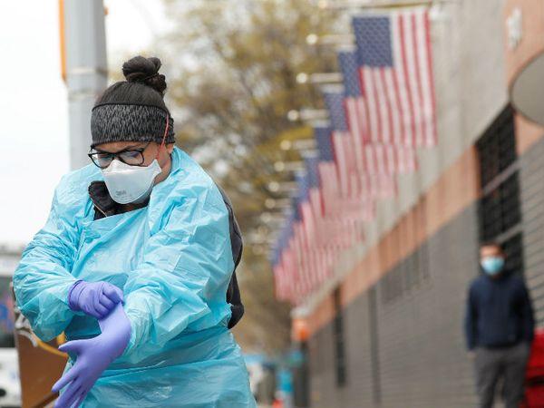 न्यूयॉर्क के एल्महर्स्ट हॉस्पिटल में जाने से पहले एक इमरजेंसी मेडिकल टेक्नीशियन (ईएमटी) पीपीई पहनती हुई। न्यूयॉर्क अमेरिका में कोरोना से सबसे ज्यादा प्रभावित है। - Dainik Bhaskar