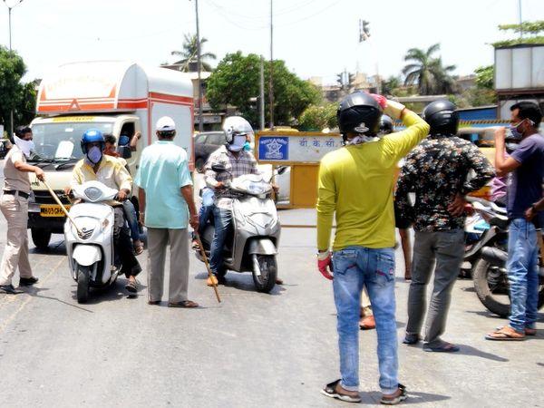 कोरोना अनलॉक के बीच धारावी इलाके में बढ़ रही भीड़ को रोकते हुए पुलिसकर्मी।