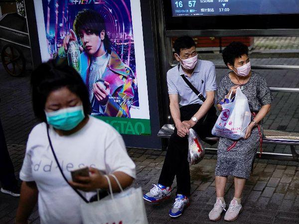 यह तस्वीर शंघाई के एक बस स्टॉप की है। महामारी से बचने के लिए लोग मास्क पहनकर बस का इंतजार कर रहे हैं।