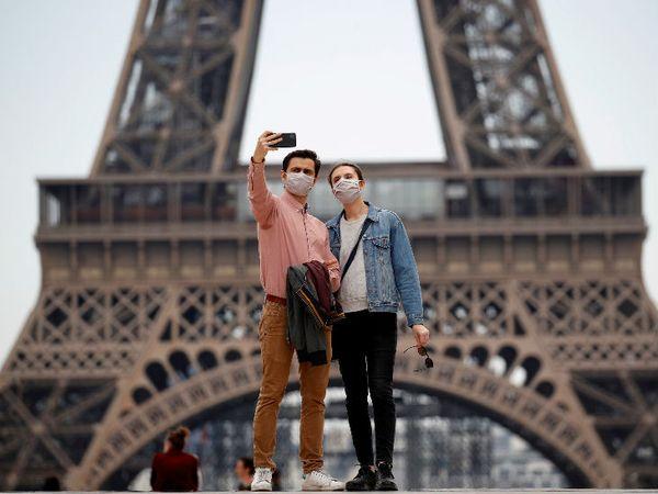 पेरिस स्थित एफिल टावर के पास मास्क पहनकर सेल्फी लेते लोग। द्वितीय विशव युद्ध के बाद पहली बार यह तीन महीने से ज्यादा समय तक बंद रहा। (फाइल फोटो)