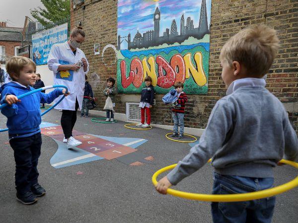 यह तस्वीर लंदन के एक स्कूल की है, जहां बच्चे सोशल डिस्टेंसिंग के नियम का पालन करते हुए खेल रहे हैं।