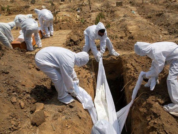 नई दिल्ली स्थित एक कब्रिस्तान में कोरोनावायरस मृतक को दफनाते कर्मी, भारत में संक्रमण के रोज करीब 10 हजार मामले सामने आ रहे हैं