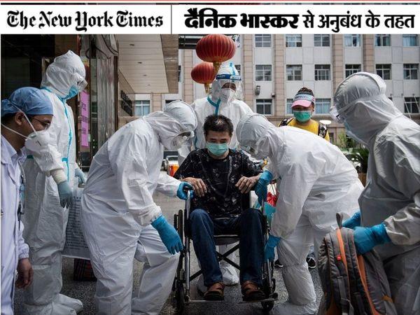 चीन के वुहान में कोविड 19 से ठीक हुए मरीज को ले जाने में मदद करते स्वास्थ्य कर्मी। - Dainik Bhaskar