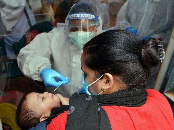 यह फोटो नई दिल्ली की है। शुक्रवार को यहां न्यू अशोक नगर में राजकीय सर्वोदय कन्या विद्यालय में एक स्वास्थ्यकर्मी ने बच्चे का स्वैब सैंपल लिया। - Dainik Bhaskar