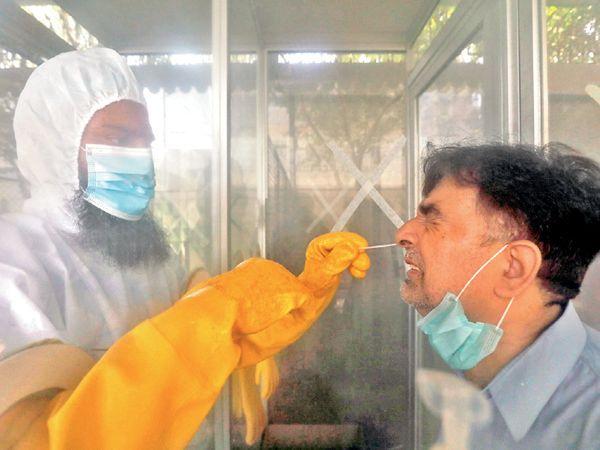 कराची के अस्पताल में डॉक्टर संदिग्ध मरीज के स्वाब का सैपल ले रहे हैं। पाकिस्तान में रोज 20 हजार टेस्ट किए जा रहे हैं। - Dainik Bhaskar