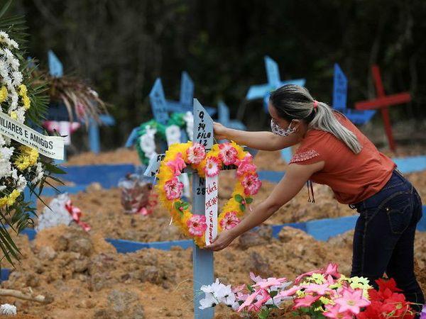 ब्राजील में शुक्रवार को करीब 47 हजार नए संक्रमित सामने आए। फोटो मनाउस शहर के कब्रिस्तान का है। यहां एक महिला कोविड-19 से मारे गए रिश्तेदार की कब्र पर फूल चढ़ाने पहुंची।