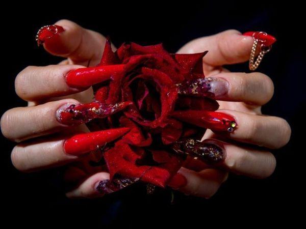 लाल गुलाब से मिलते जुलते रेड के शेड का इस्तेमाल नाखूनों की खूबसूरती बढ़ाने में किया गया है। इस नेल आर्ट में रेड फेदर, कलरफुल क्रिस्टल और छोटी-छोटी चेन से नाखूनों को सजाया गया है।