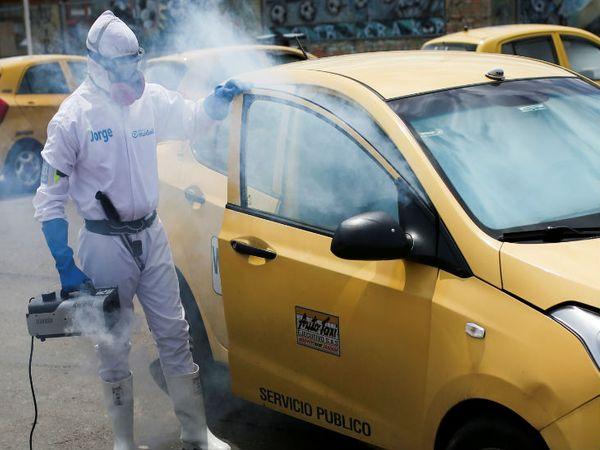 कोलंबिया की राजधानी बोगोटा में रविवार को कार सैनिटाइज करता सरकारी कर्मचारी। नए मामले बढ़ने के बाद 1 जुलाई से लॉकडाउन बढ़ा दिया गया है।
