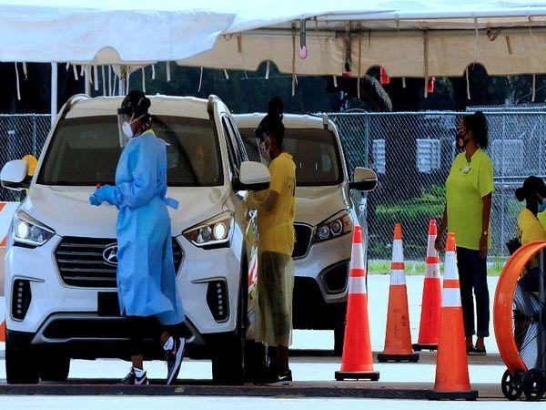 अमेरिका के फ्लोरिडा में रविवार को एक टेस्टिंग सेंटर पर लोगों की जांच में जुटी स्वास्थ्यकर्मी। यहां नए मामले बढ़ने के बाद टेस्टिंग भी तेज कर दी गई है।