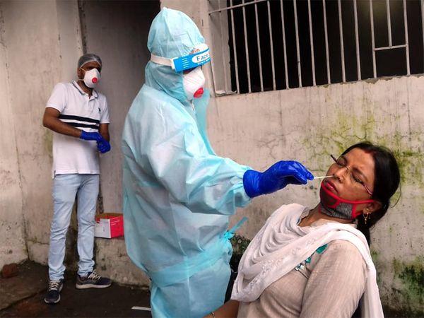 कोरोना संक्रमण की जांच के लिए महिला का सैंपल लेते डॉक्टर। - Dainik Bhaskar