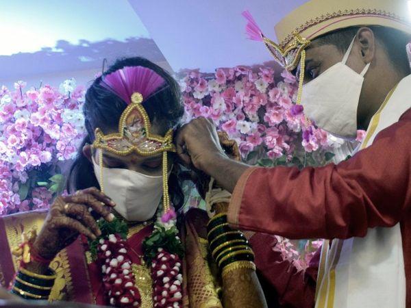 मुंबई में कोरोनावायरस महामारी के बीच दूल्हे योगेश पंचले और दुल्हन समीक्षा ने मास्क पहनकर शादी की रस्में की हैं।