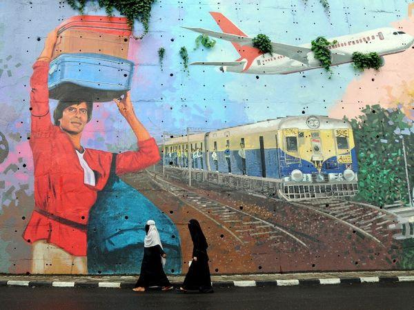 मुंबई में बॉलीवुड अभिनेता अमिताभ बच्चन की 1983 की फिल्म 'कुली' की एक ग्राफिटी के सामने से गुजरती हुईं दो महिलाएं।