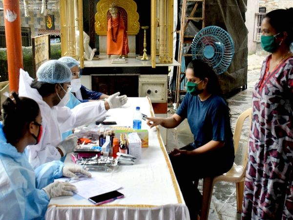 पीपीई किट पहनकर स्वास्थ्य कर्मचारी मुंबई में घाटकोपर में लोगों का मेडिकल चेकअप करते हुए।
