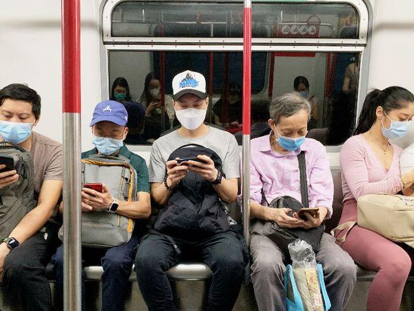 हॉन्गकॉन्ग मेट्रो में मास्क पहनकर यात्रा करते लोग। एक हफ्ते के भीतर यहां संक्रमितों की संख्या बढ़ी है। इसके चलते यहां सोशल डिस्टेंसिंग के नियम भी सख्त कर दिए गए हैं।