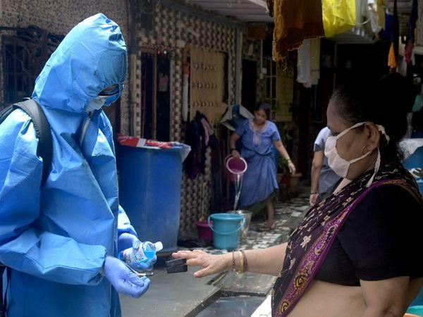 यह तस्वीर मुंबई के मलाड में कुरार गांव की है। यहां पीपीई किट पहनकर स्वास्थ्य कर्मचारी सर्वे कर रहे हैं।  एक महिला से उनकी स्वास्थ्य डिटेल ली और बीपी चेक किया गया। - Dainik Bhaskar