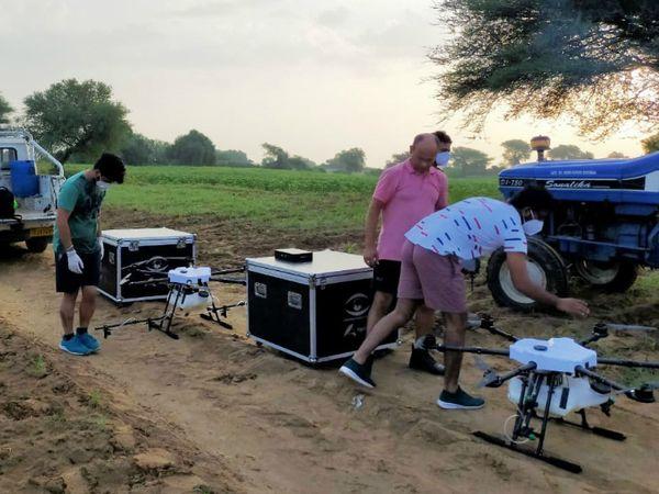 लोहारू क्षेत्र में टिडि्डयों से बचाव को लेकर ड्रोन से दवा छिड़काव की तैयारी करते टीम सदस्य। - Dainik Bhaskar