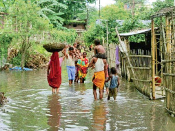 घुटने भर जमे पानी में होकर गुजरते लोग। - Dainik Bhaskar