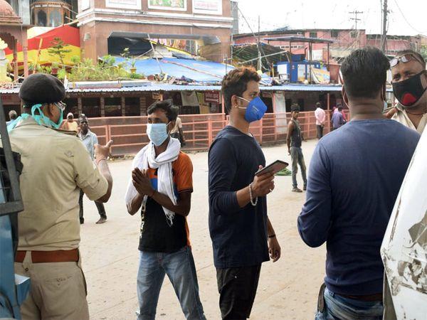 लॉकडाउन के दौरान सड़क पर निकले युवकों को रोकते पुलिसकर्मी।
