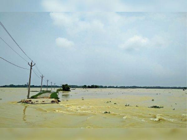 करहारा गांव के मुख्य पथ पर बहता बाढ़ का पानी।