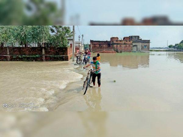 बहलोलपुर में सड़क पर लगा पानी और इससे होकर गुजरते लोग। - Dainik Bhaskar