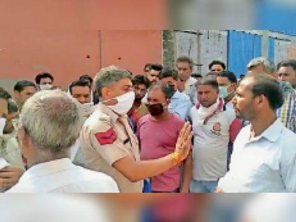 यमुनानगर। फैक्ट्री के सफाई कर्मचारी की मौत पर हंगामा करते परिजनों को समझाता पुलिस कर्मचारी। - Dainik Bhaskar