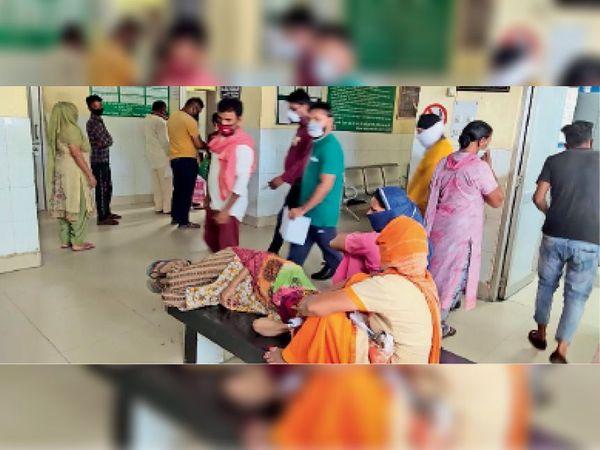 ओपीडी में डॉक्टर के इंतजार में खड़े लोग और बैंच पर लेटी बुजुर्ग महिला। - Dainik Bhaskar