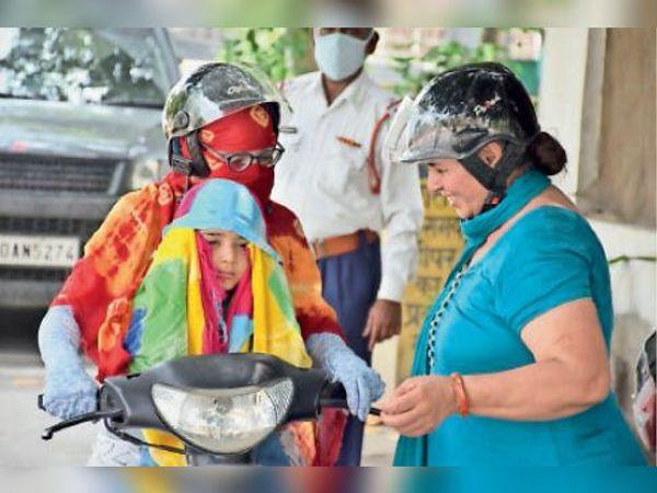 फव्वारा चौक पर गर्मी व धूप से बचाव के लिए बच्चे को कपड़ा ओढ़ाते हुए। मंगलवार काे अधिकतम तापमान 37.4 डिग्री रहा। - Dainik Bhaskar