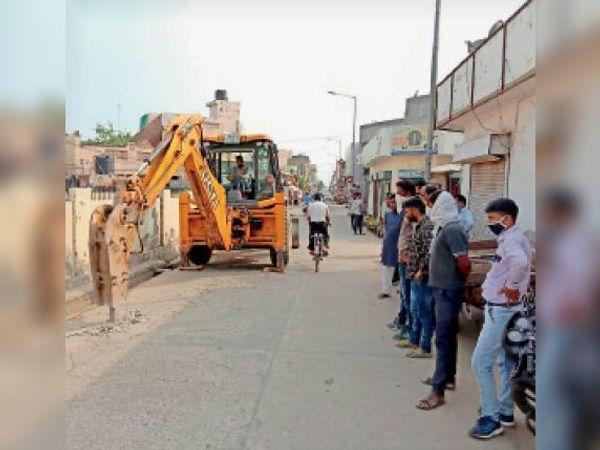 बब्याल रोड पर पोल लगाने के लिए सड़क तोड़ती अर्थ मूविंग मशीन। - Dainik Bhaskar
