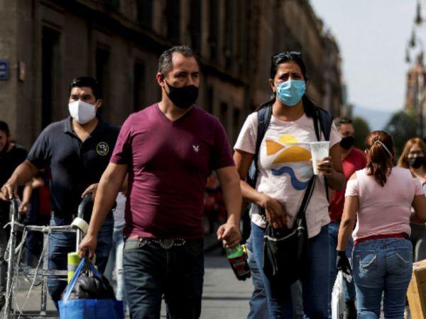 मैक्सिको की राजधानी न्यू मैक्सिको सिटी के जोकालो स्क्वॉयर पर सोमवार को मास्क लगाकर जाते लोग।