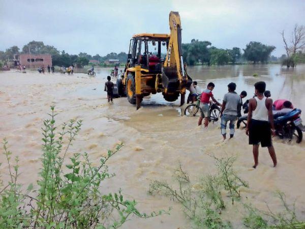 भौगाछी की सड़कों पर बह रहा बाढ़ का पानी व उसमें फंसी जेसीबी, बाइक और आते-जाते लोग। - Dainik Bhaskar
