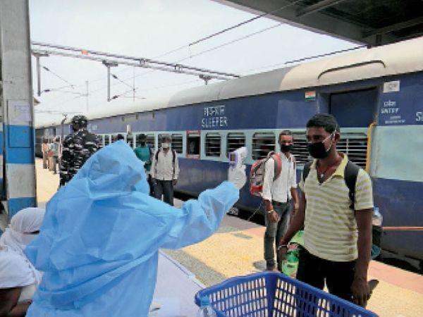 स्टेशन पर यात्रियों की थर्मल स्क्रीनिंग करते कर्मचारी। - Dainik Bhaskar