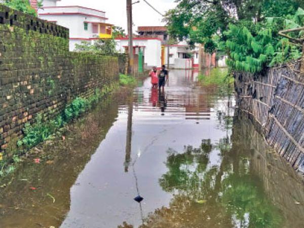 ड्रेनेज सिस्टम फेल होने के कारण तेघरिया इंदर वाड़ी में जमे पानी से गुजरते महिला व बच्चें । - Dainik Bhaskar
