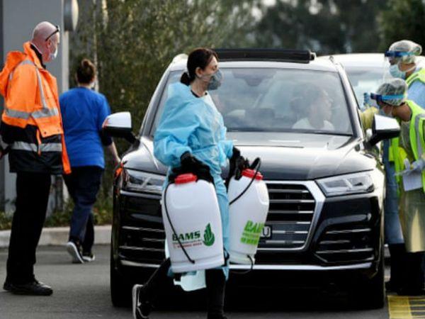 ऑस्ट्रेलिया के सिडनी में बीते शनिवार को क्रॉसरोड होटल से बाहर निकलती एक मेडिकल वर्कर। होटल में कुछ संक्रमित मिलने के बाद इसे सील किया गया है।