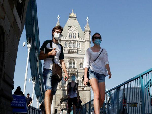ब्रिटेन की राजधानी लंदन में शुक्रवार को मास्क लगाकर टॉवर ब्रिज से गुजरते लोग। सरकार ने कहा है कि फिलहाल सभी के लिए मास्क लगाना जरूरी है।